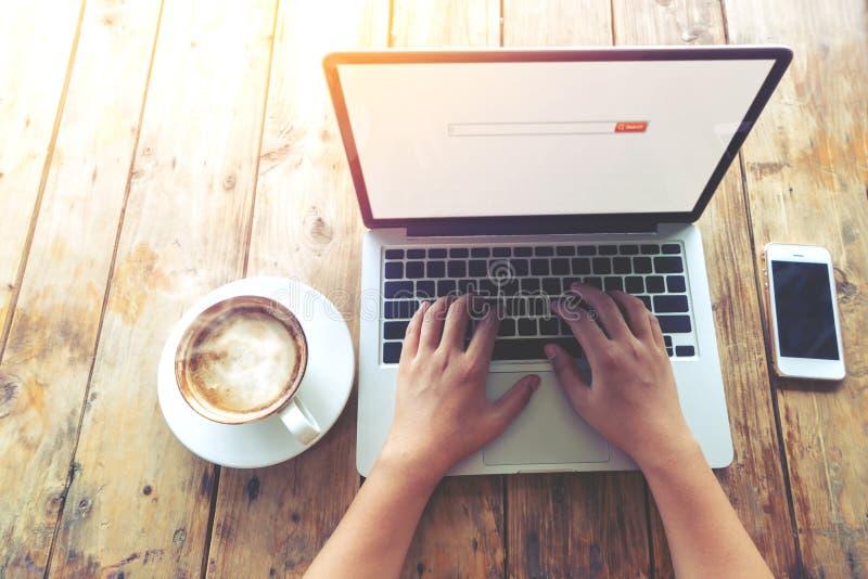 o ` novo bonito s da mulher do moderno entrega o trabalho ocupado em seu portátil que senta-se na tabela de madeira em uma cafeta imagens de stock