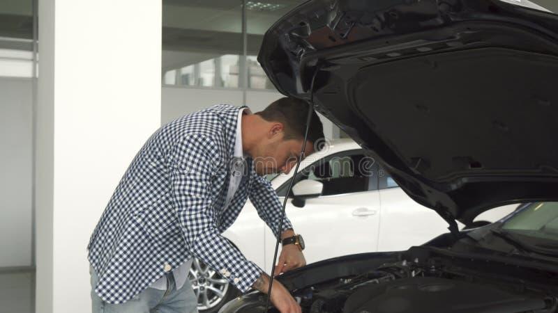O novo proprietario do carro estuda os detalhes em uma capa aberta foto de stock