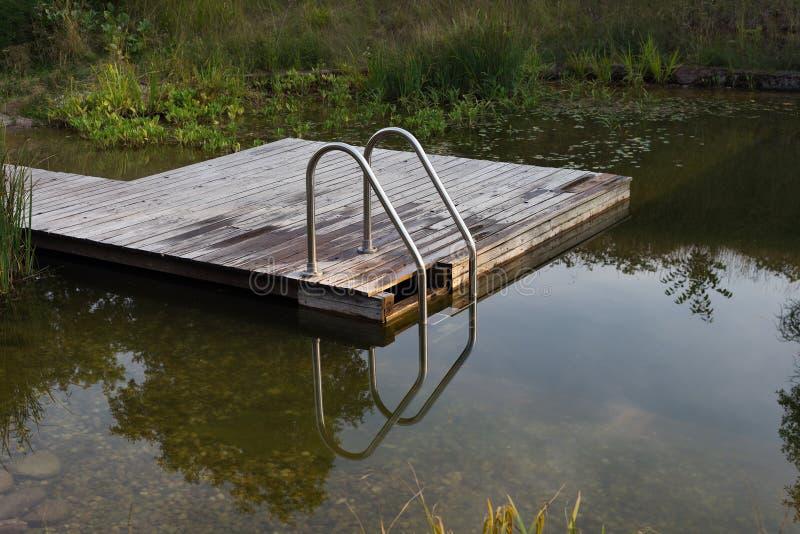 O NSP de madeira do cais da plataforma das escadas naturais da lagoa da piscina jardina biótopo da água imagem de stock