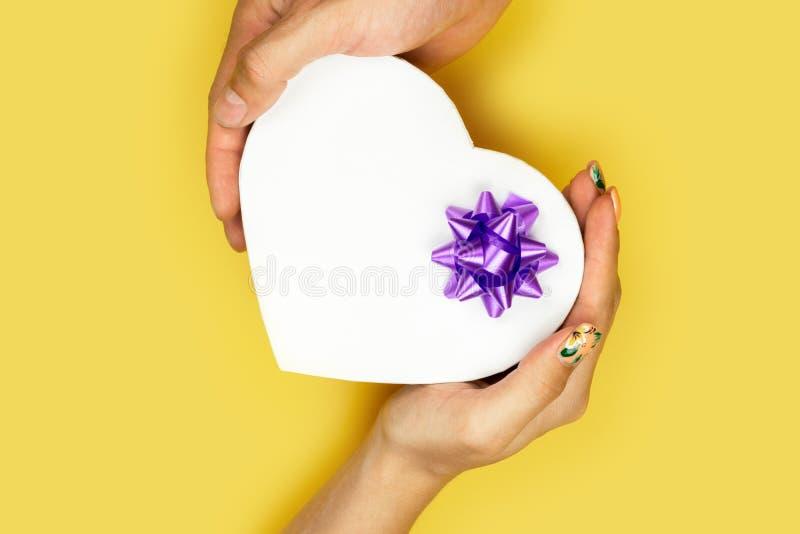 A?o Nuevo, concepto de la Navidad Un par joven que sostiene una caja de regalo en la forma de un corazón Valentine Gift de foto de archivo