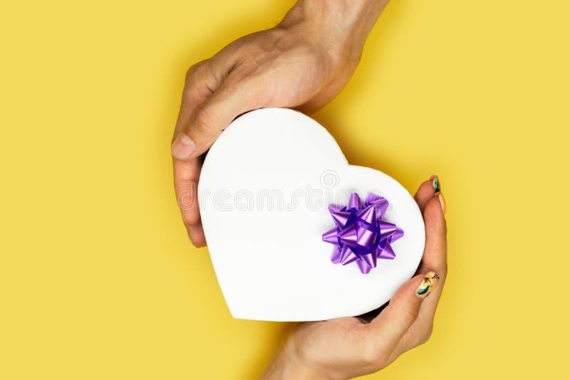A?o Nuevo, concepto de la Navidad Un par joven que sostiene una caja de regalo en la forma de un corazón Valentine Gift de fotografía de archivo libre de regalías
