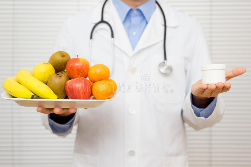O nutricionista do doutor oferece o paciente escolher fotografia de stock