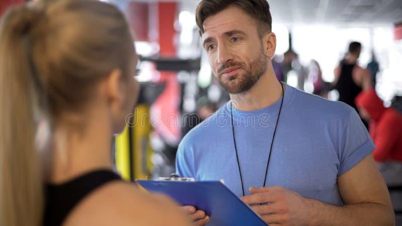 O nutricionista explica o cliente fêmea sobre o equilíbrio apropriado da nutrição e de água imagem de stock