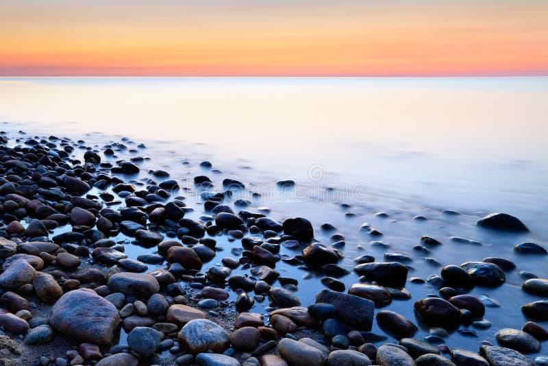 O oceano do por do sol apedreja o fundo Costa de mar Báltico foto de stock royalty free