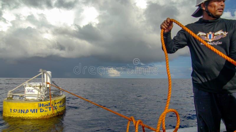 O oficial do departamento meteorológico tailandês arrasta a boia da detecção do tsunami para mudar a boia nova no mar de Andaman fotografia de stock royalty free