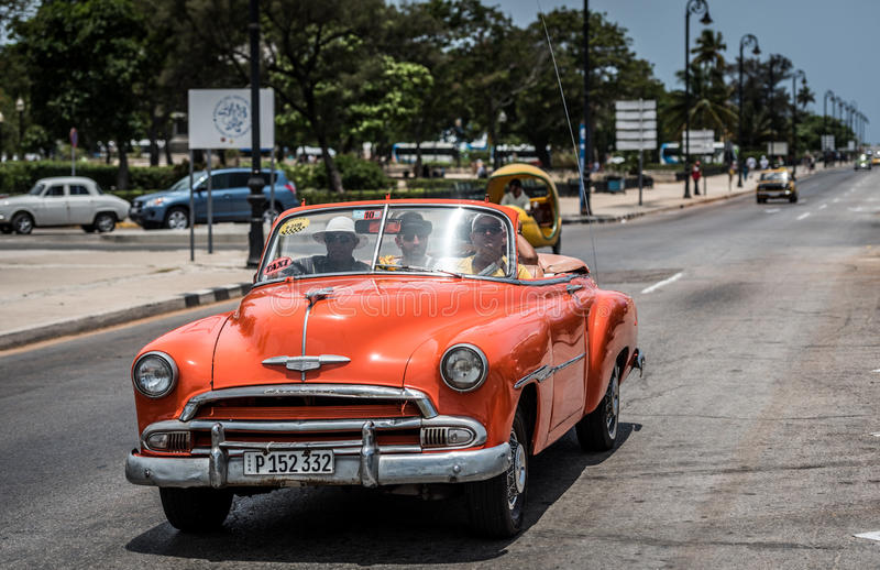 O Oldtimer americano alaranjado de HDR Cuba conduz no passeio Malecon em Havana imagem de stock