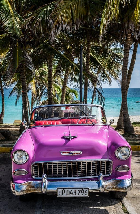 O Oldtimer americano cor-de-rosa de HDR Cuba estacionou sob as palmas perto da praia em Varadero fotos de stock royalty free