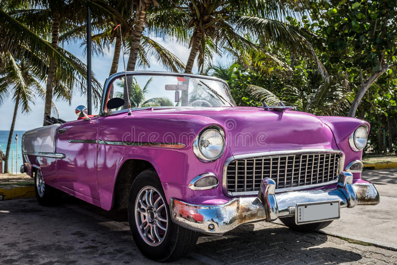 O Oldtimer cor-de-rosa americano de HDR Cuba estacionou perto da praia fotografia de stock