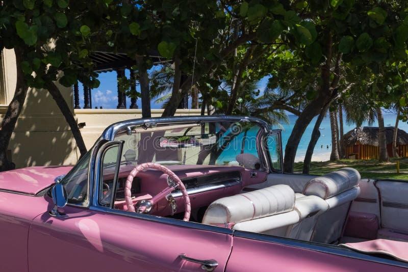 O Oldtimer cor-de-rosa americano do Cabriolet estacionou perto da praia em Varadero Cuba - reportagem 2016 de Serie Kuba foto de stock