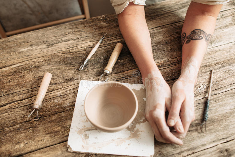 O oleiro cansado entrega perto da cerâmica na tabela de madeira fotos de stock royalty free