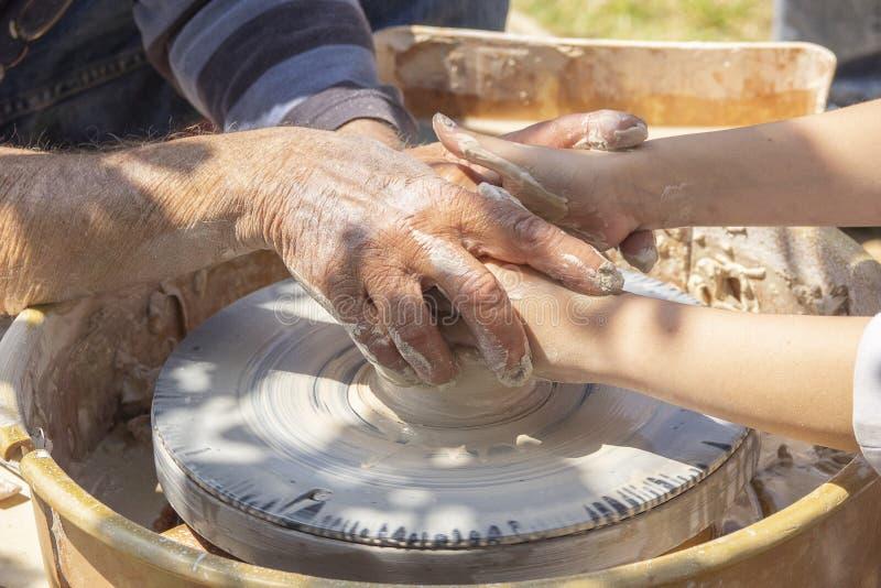 O oleiro ensina um estudante criar a cerâmica Espaço de trabalho exterior Molde da argila fotografia de stock royalty free