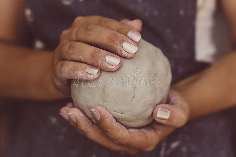 O oleiro fêmea entrega guarda a argila para a cerâmica, foco seletivo fotografia de stock royalty free