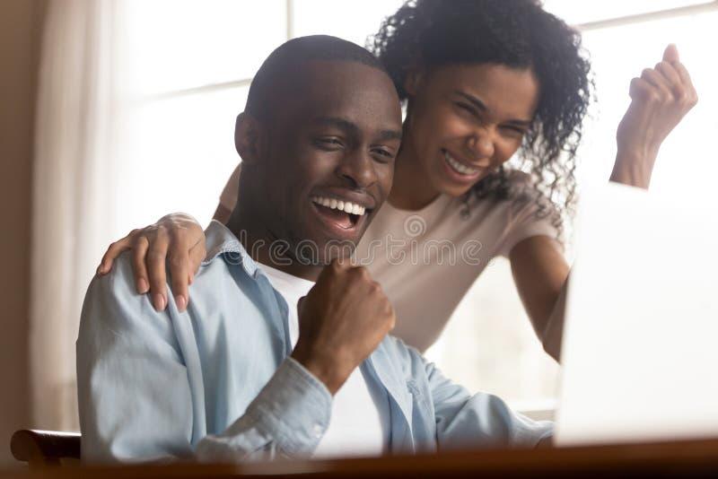 O olhar africano dos pares no computador sente excitado comemorando a vitória da loteria foto de stock
