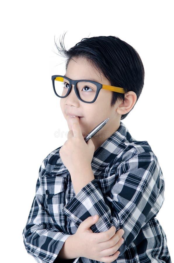 O olhar bonito do rapaz pequeno como pensa sobre aquele com o isolador dos vidros do olho imagem de stock royalty free