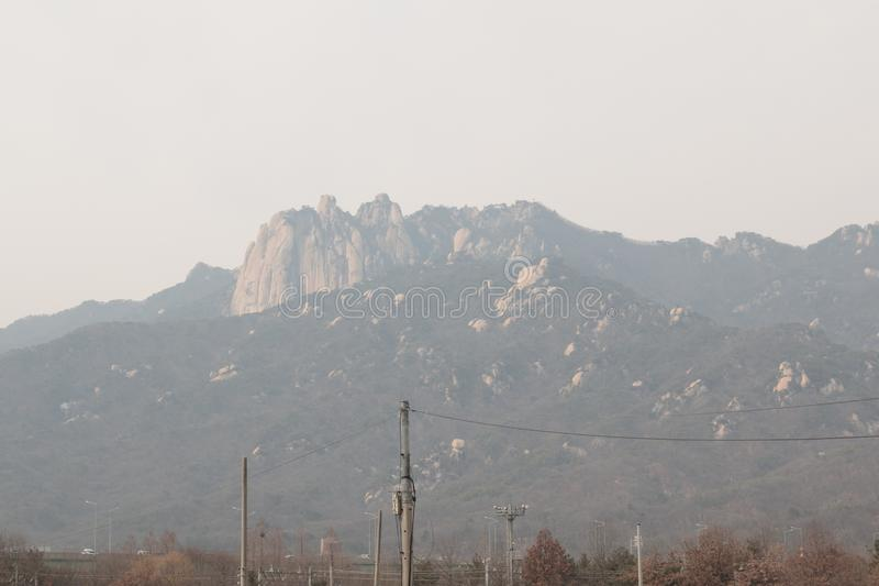 O olhar da montanha borrou devido à poluição do ar fina densa da poeira em Seoul imagens de stock royalty free