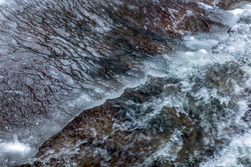 O olhar detalhado na água corre sob o gelo em um rio foto de stock