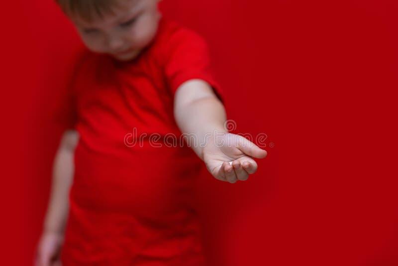 O olhar do rapaz pequeno para baixo e puxa sua mão para a câmera, criança quis a ajuda para ele imagens de stock