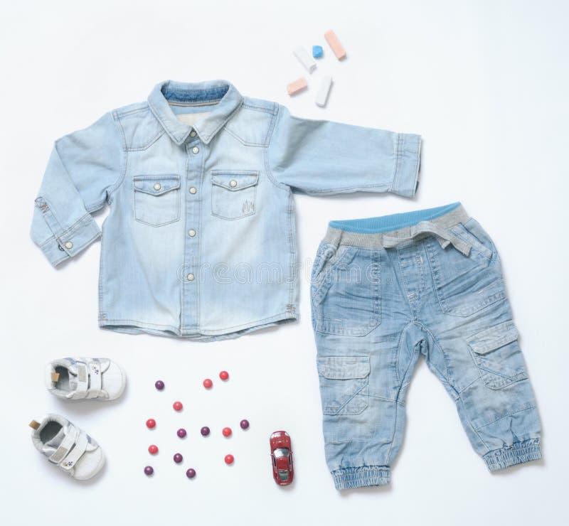 O olhar na moda da sarja de Nimes da vista superior do bebê veste-se com brinquedo e snea imagem de stock royalty free