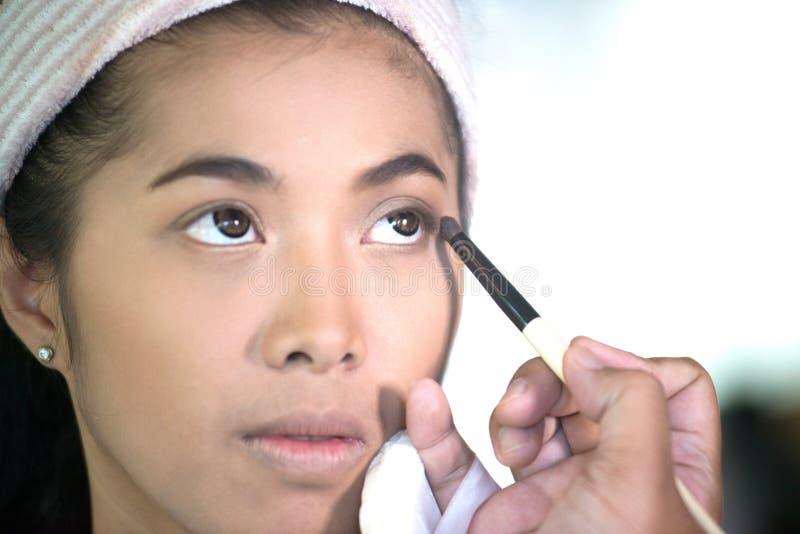 O olho asiático bonito da mulher compõe para aplicar-se fotos de stock royalty free