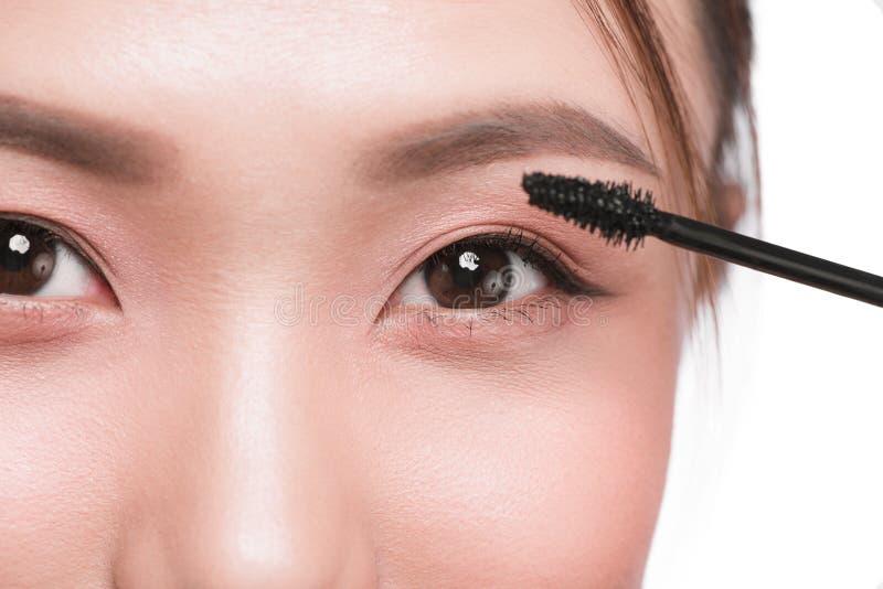 O olho compõe para aplicar-se Escova do rímel Retrato do asiático bonito w imagem de stock royalty free