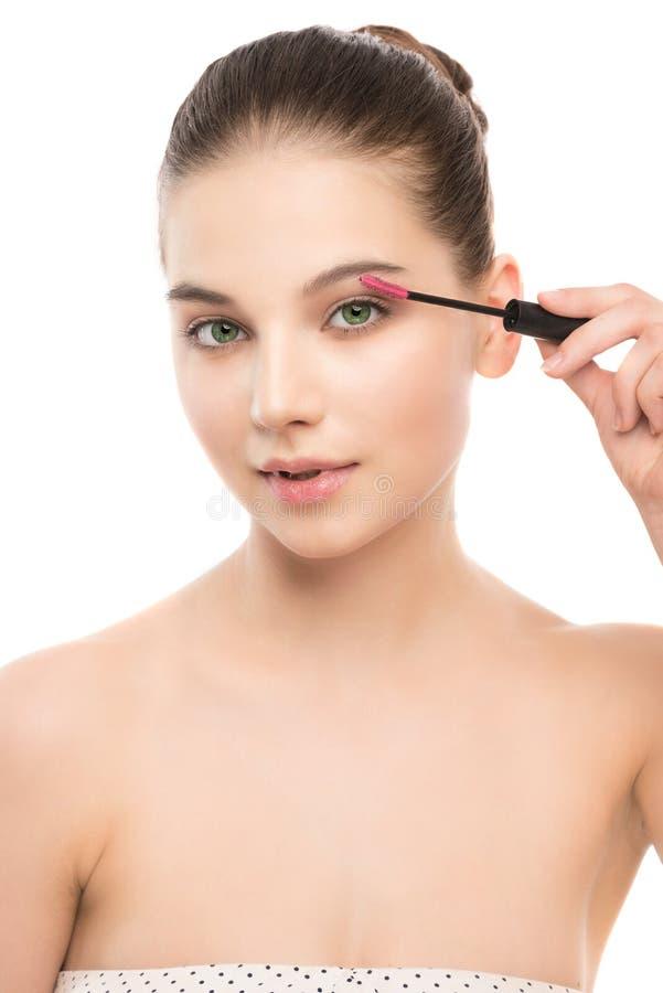 O olho compõe para aplicar-se Rímel que aplica o close up, chicotes longos Escova da composição Isolado imagem de stock royalty free
