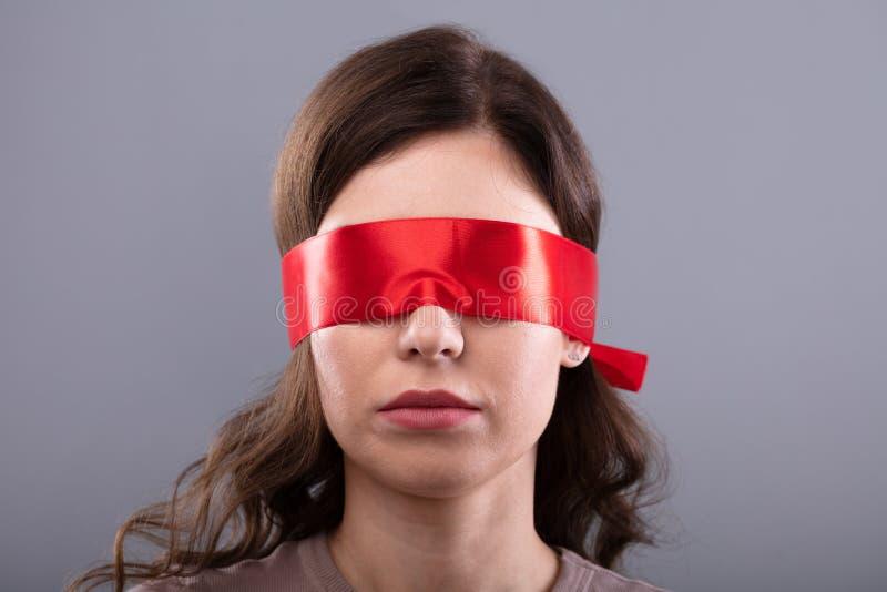 O olho da mulher cobriu com a fita vermelha fotografia de stock