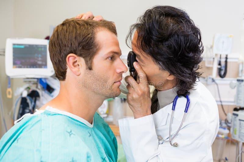 O olho do paciente do doutor With Ophthalmoscope Examining fotos de stock