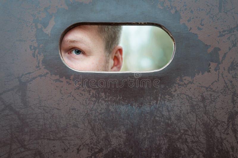 O olho do ` s do homem está espiando através de um furo oval imagem de stock