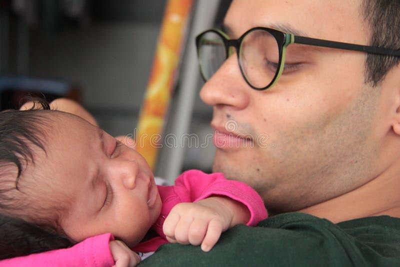 O ombro do pai de abraço de sono da menina infantil fotos de stock