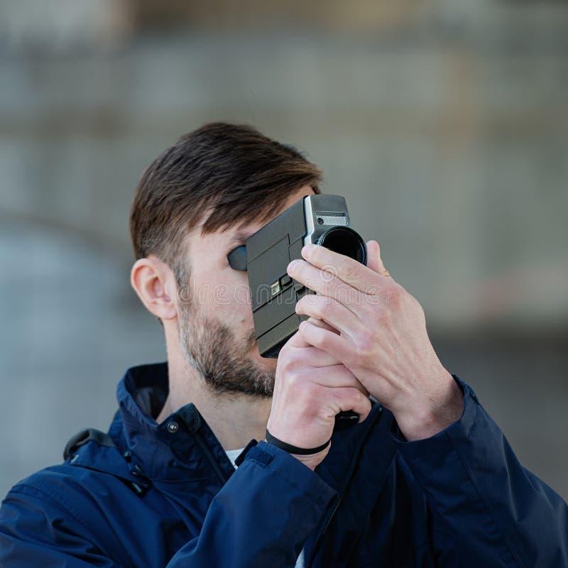 O operador cinematográfico profissional do homem farpado observa e dispara em uns 8mm mo foto de stock