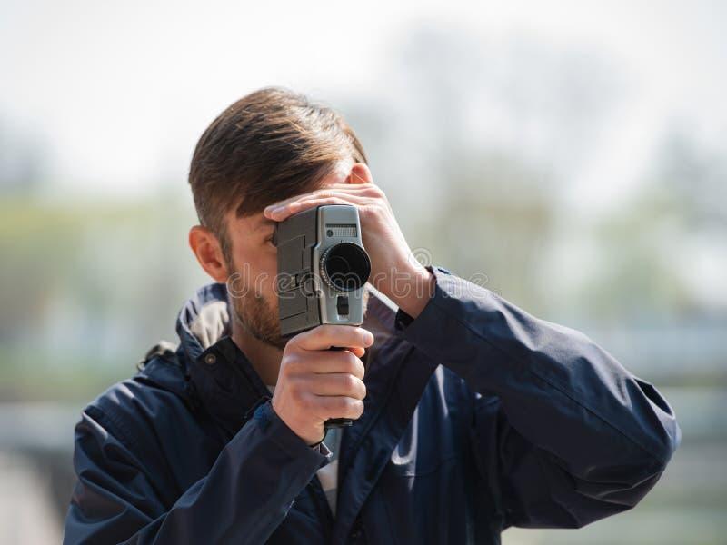 O operador cinematográfico profissional do homem farpado observa e dispara em uns 8mm mo imagens de stock