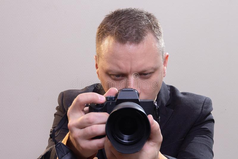 O operador cinematogr?fico video masculino novo, fot?grafo, dispara no v?deo ou toma uma foto na c?mera fotografia de stock