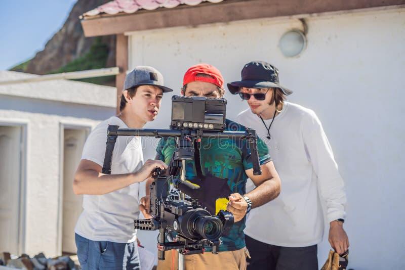 O operador, o diretor e o dp da câmera discutem o processo de um tiro video comercial fotos de stock royalty free