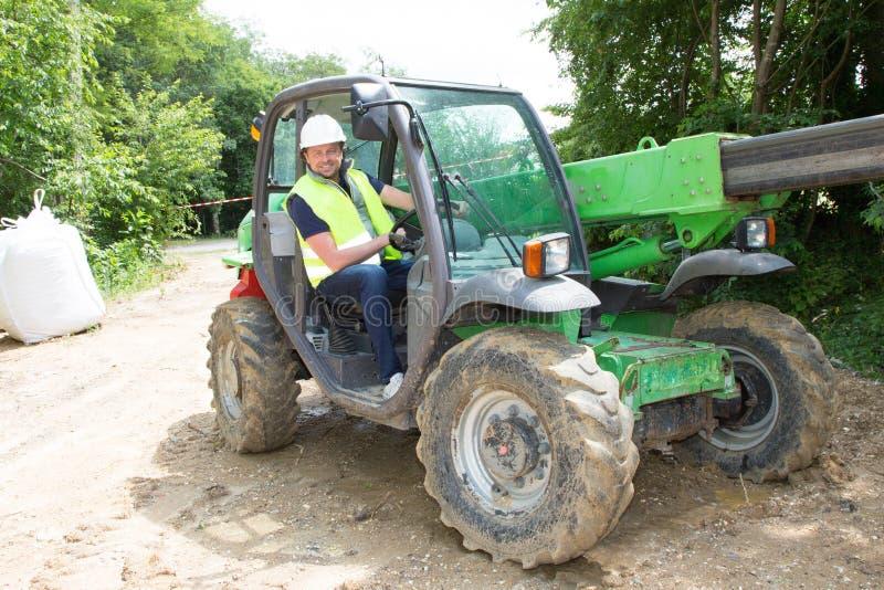 O operador do homem do motorista da máquina escavadora com metal segue o descarregamento do solo na construção fotos de stock