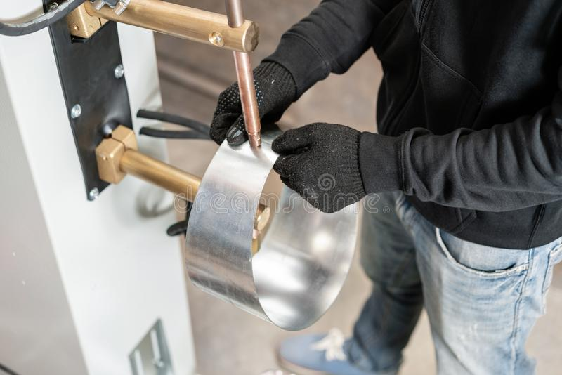 O operador está trabalhando com processo da soldadura de ponto Duas partes de aço são derretidas junto pelo calor elétrico a prod fotos de stock