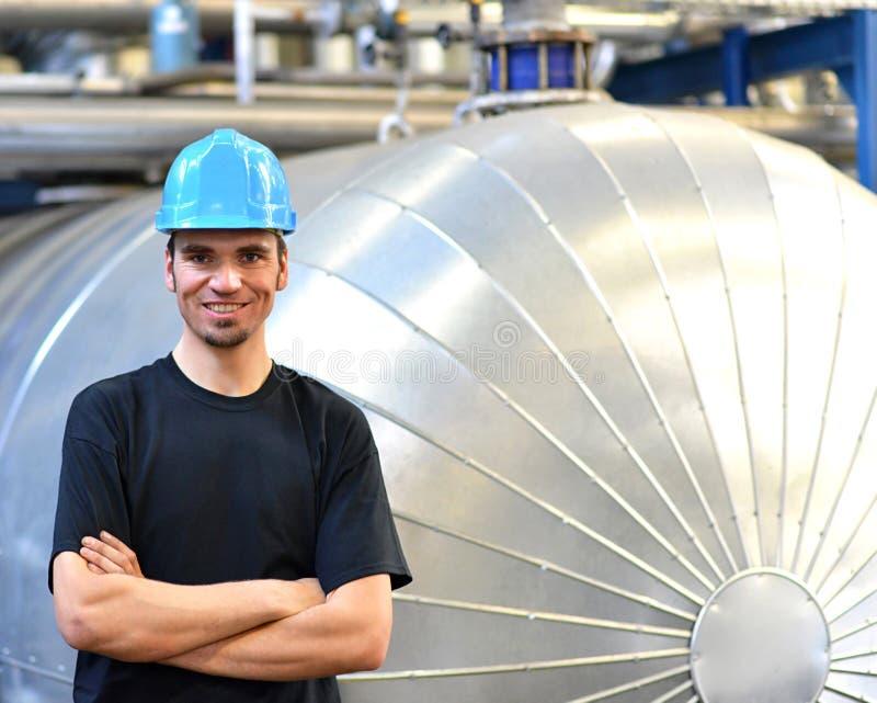 O operador repara uma máquina em uma planta industrial com ferramentas imagem de stock royalty free