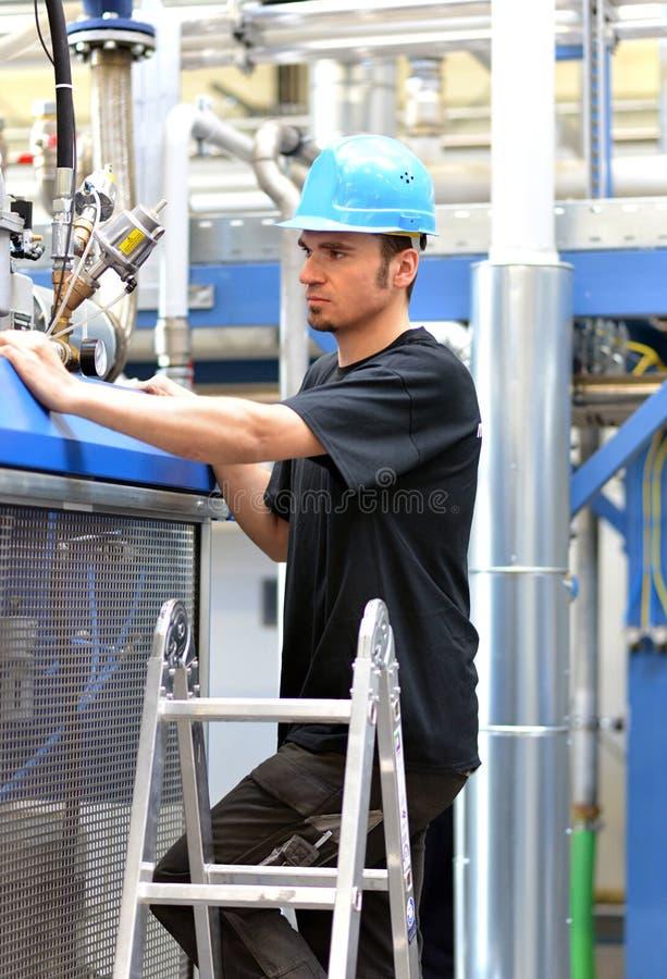 O operador repara uma máquina em uma planta industrial com ferramentas imagem de stock