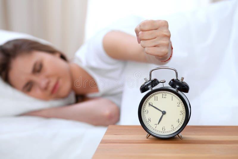 O oposto do despertador da jovem mulher sonolento que estica a mão a querer de soada do alarme desliga-o Acorde cedo, não foto de stock royalty free