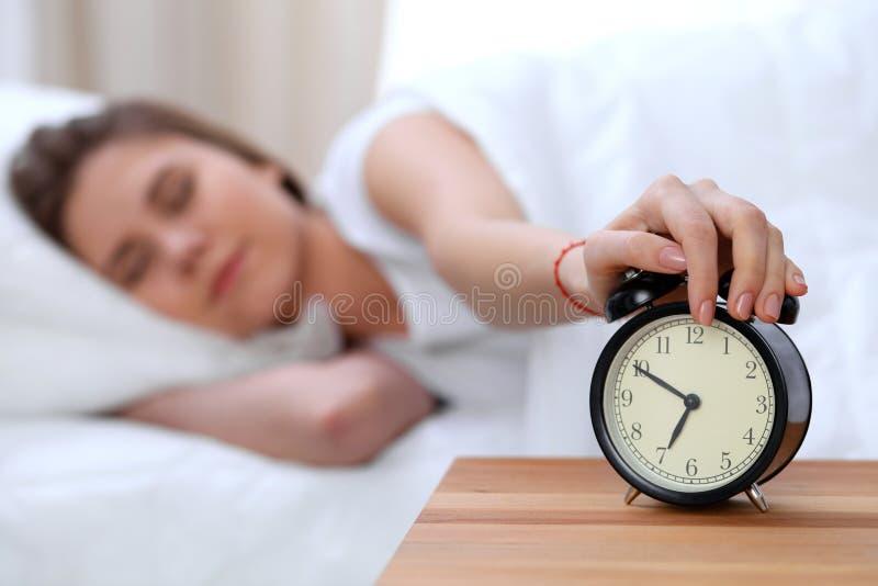 O oposto do despertador da jovem mulher sonolento que estica a mão a querer de soada do alarme desliga-o Acorde cedo, não imagens de stock