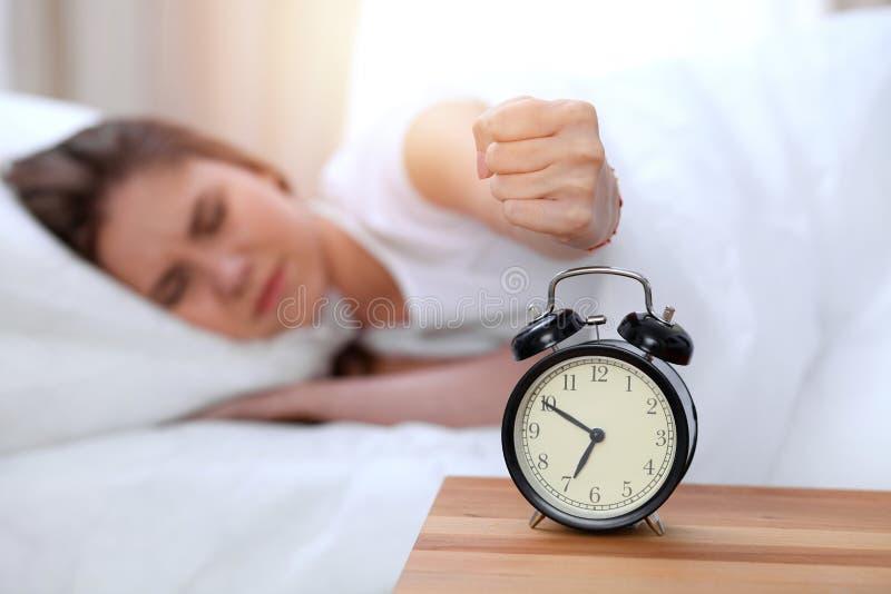 O oposto do despertador da jovem mulher sonolento que estica a mão a querer de soada do alarme desliga-o Acorde cedo, não fotografia de stock