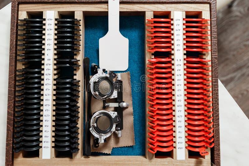 O optometrista prepara um grupo de lentes experimentais oftálmicos para os testes da visão e o quadro da experimentação, tabela a fotos de stock