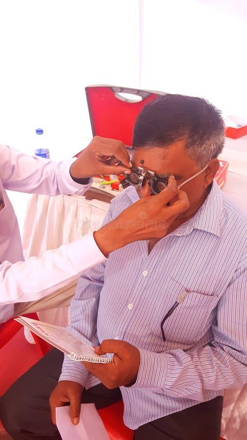 O optometrista verifica o teste da visão do olho de um ancião imagens de stock royalty free