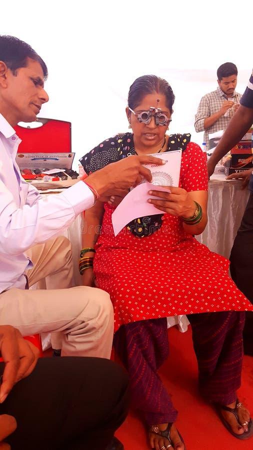 O optometrista verifica o teste da visão do olho de uma mulher adulta foto de stock royalty free