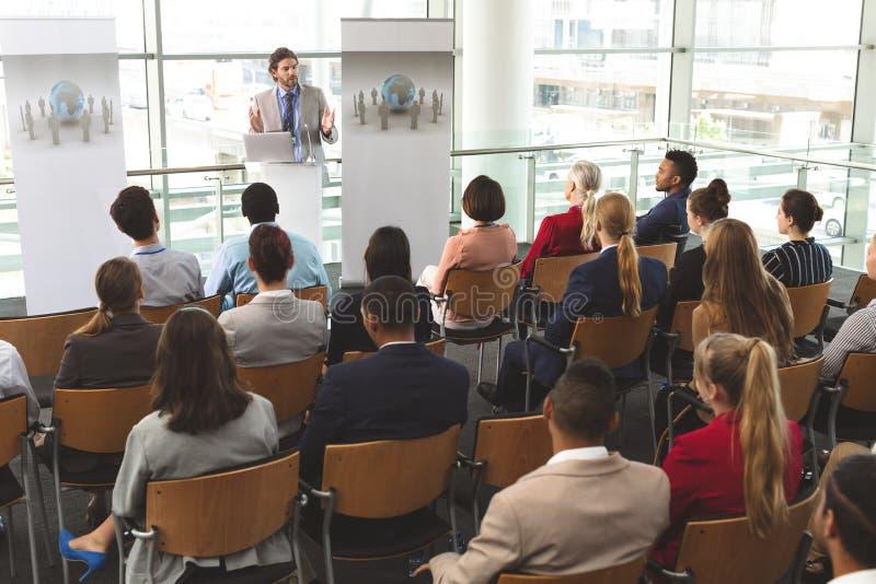 O orador masculino com portátil fala em um seminário do negócio fotos de stock royalty free