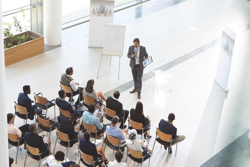 O orador masculino com tabuleta digital fala em um seminário do negócio fotos de stock