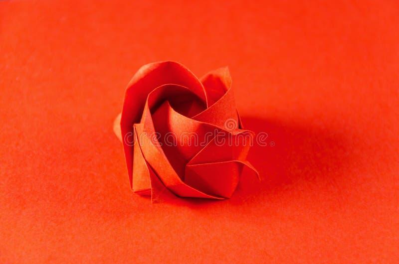 O origâmi vermelho aumentou no fundo vermelho fotografia de stock royalty free