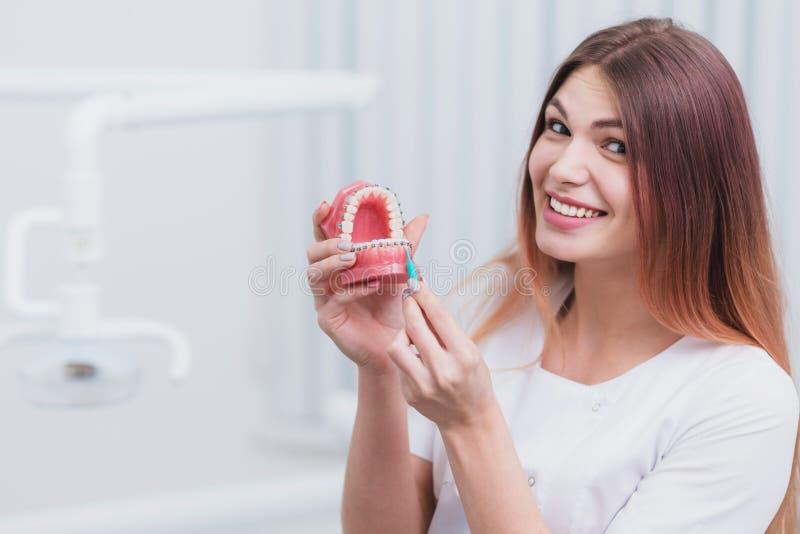 O orthodontist bonito do doutor mostra-lhe como importar-se com seus dentes fotos de stock