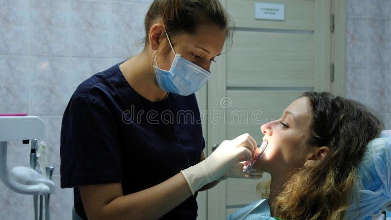 O orthodontist do dentista põe um fixator dental para que uma mulher instale um sistema do suporte Visita ao dentista foto de stock