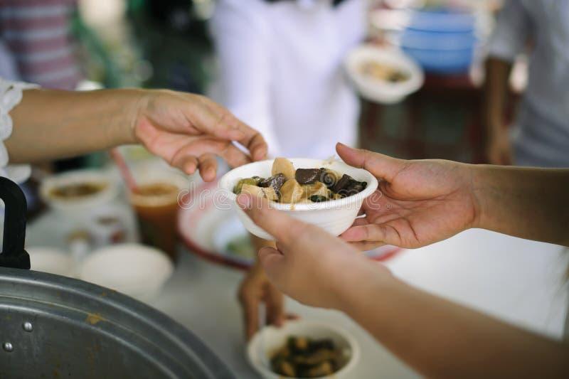 O os sem-abrigo é ajudado com relevo de alimento, relevo da fome: voluntários que dão o alimento aos povos pobres na necessidade  foto de stock royalty free