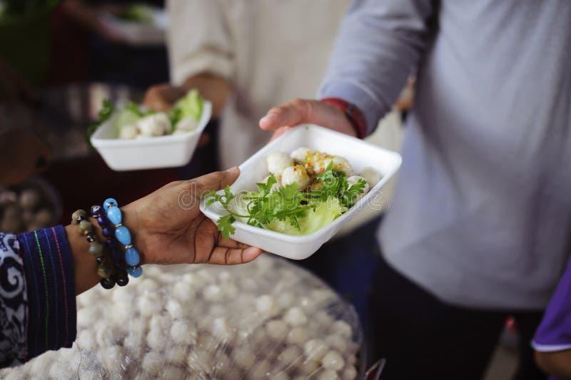 O os sem-abrigo é ajudado com relevo de alimento, relevo da fome: voluntários que dão o alimento aos povos pobres na necessidade  foto de stock